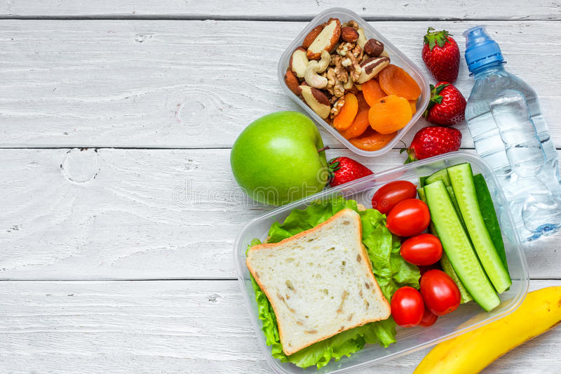 School lunch boxes with sandwich and fresh vegetables, bottle of water, nuts and fruits. On white wooden background. healthy eating concept. top view with copy royalty free stock photography