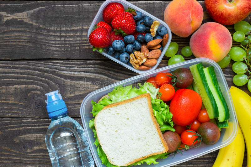 School lunch boxes with sandwich, fruits, vegetables and bottle of water and copy space stock photo