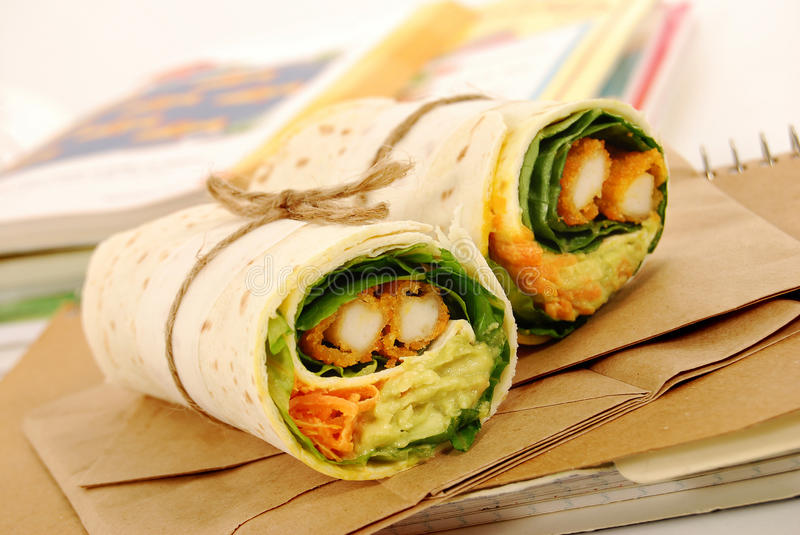 School lunch: chicken wrap sandwich with lunch bag on classroom desk royalty free stock photography