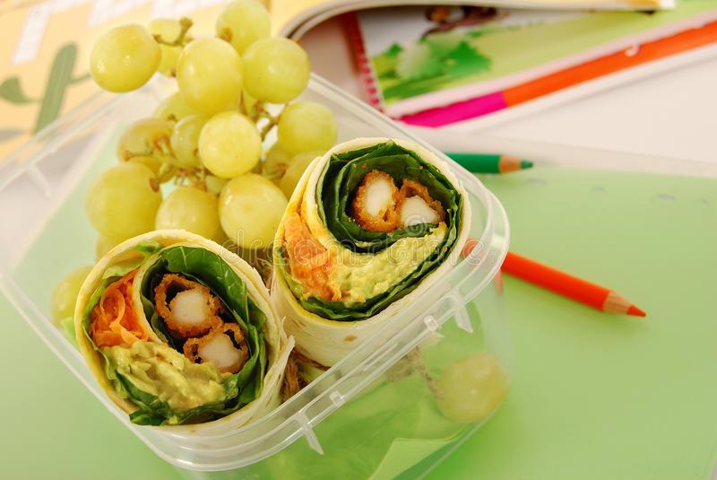 School lunch: chicken wrap sandwich in plastic box on school desk royalty free stock photos