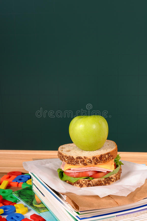 School lunch, sandwich and apple on classroom desk with blackboard, copy space, vertical royalty free stock photos