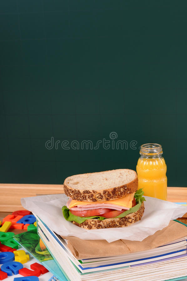 School lunch, sandwich and drink on classroom desk with blackboard, copy space, vertical stock photo