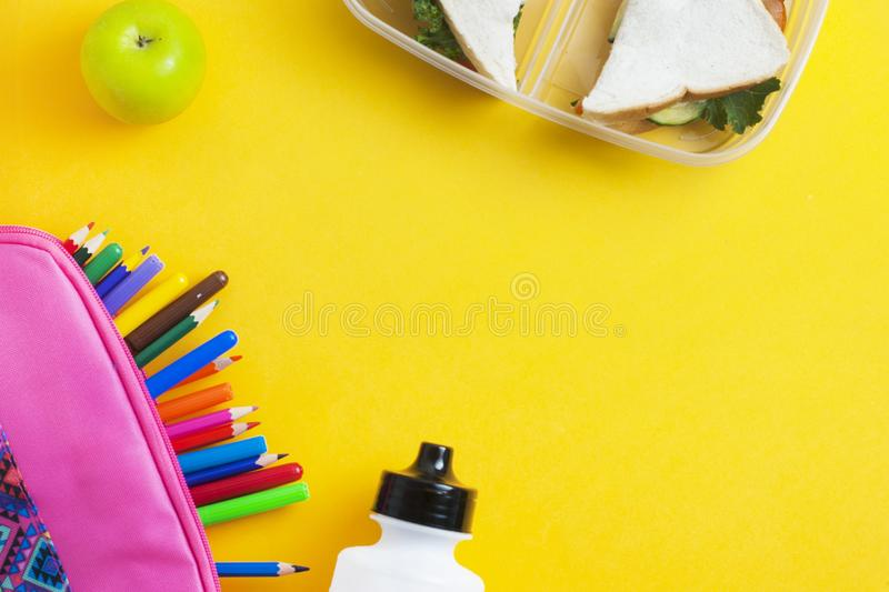 School lunch sandwich and green apple, bottle of water, healthy eating concept, colorfu encils yellow background, top view with co. School lunch sandwich and stock photography