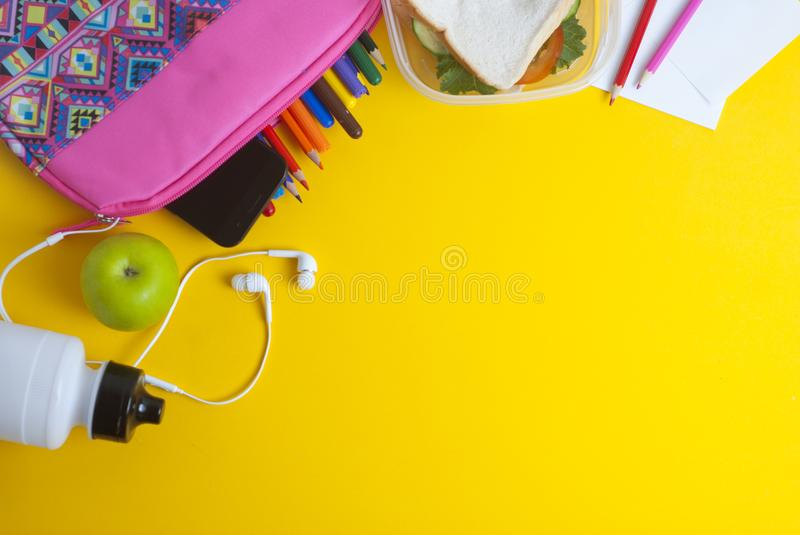 School lunch sandwich and green apple, bottle of water, healthy eating concept, colorfu encils yellow background, top view with co. School lunch sandwich and stock photo