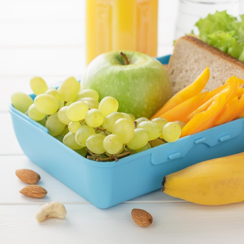 School lunchbox or bento with sandwich, fruits, vegetables, nuts and juice on white wooden background. royalty free stock photography