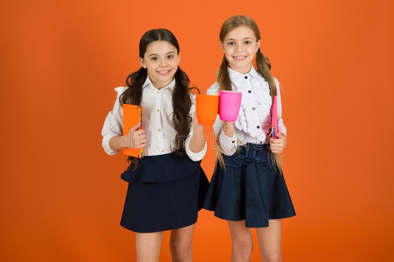 School mates relaxing with drink. Enjoy being pupil. Girls kids school uniform orange background. Schoolgirl hold book. Or notepad and mug. School routine stock photos