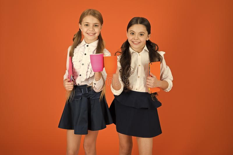 School mates relaxing with drink. Enjoy being pupil. Girls kids school uniform orange background. Schoolgirl hold book. Or notepad and mug. School routine stock image