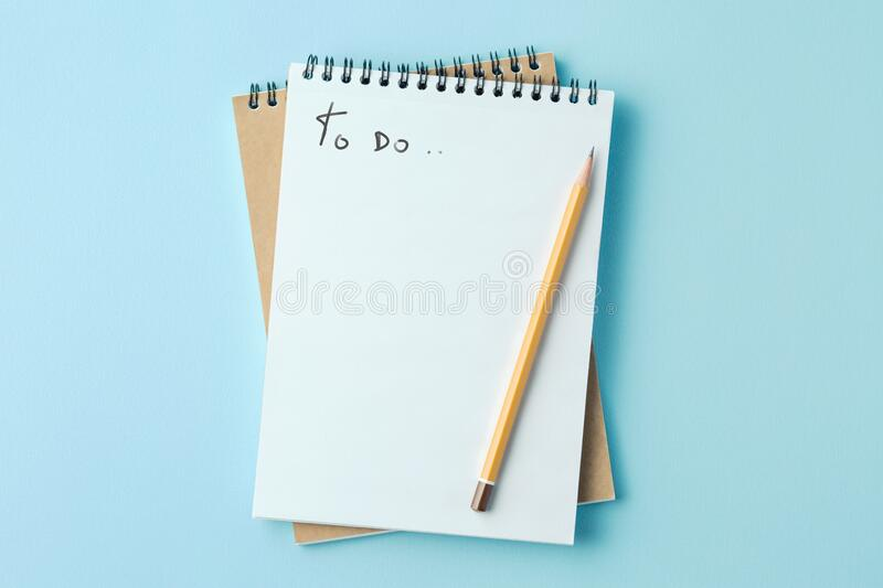 School notebook on a blue background. Spiral notepad on a table, to do list royalty free stock photo
