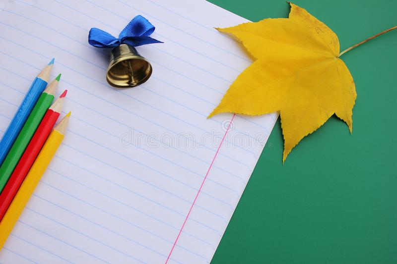 School notebook with a colored pencils and a bell next to an autumn maple leaf on a green background. Copy Space stock photo