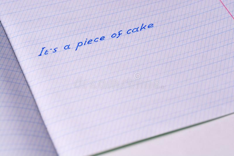 School notebook with phrase `It`s a piece of cake`. stock photo