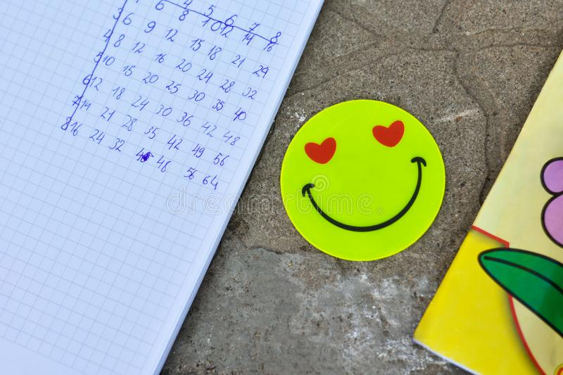School notebooks with flicker emoticon on outdoor tiles, multiplication table. School notebooks with yellow flicker emoticon on outdoor tiles, multiplication stock images