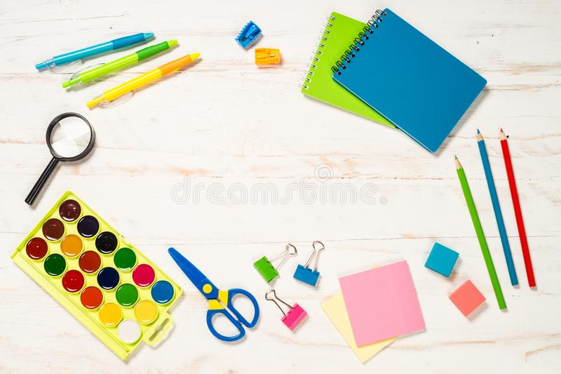 School and office sstationery on white background. Notebook, notepad, pen, pencils, loupe, paper clips and other. Top view with copy space royalty free stock photo