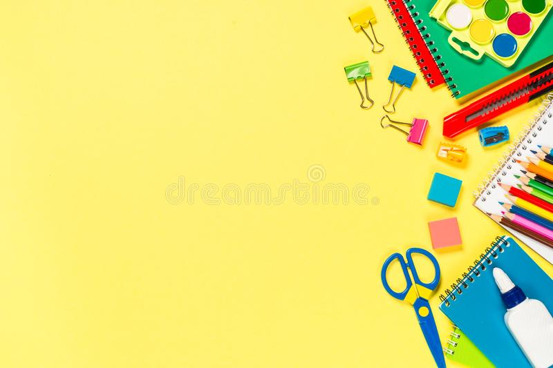 School and office sstationery on yellow background. Notebook, notepad, pen, pencils, loupe, paper clips and other. Top view with copy space royalty free stock image