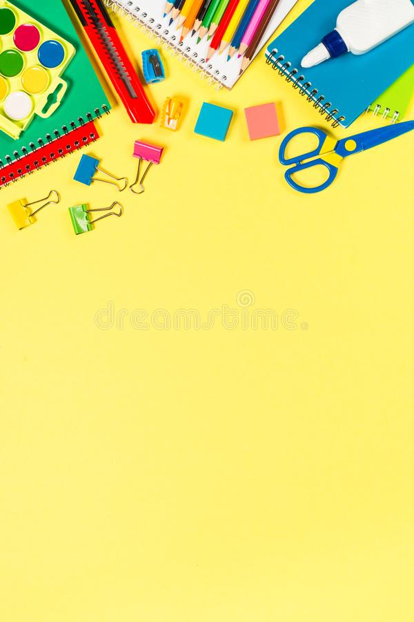 School and office sstationery on yellow background. Notebook, notepad, pen, pencils, loupe, paper clips and other. Top view with copy space royalty free stock photography