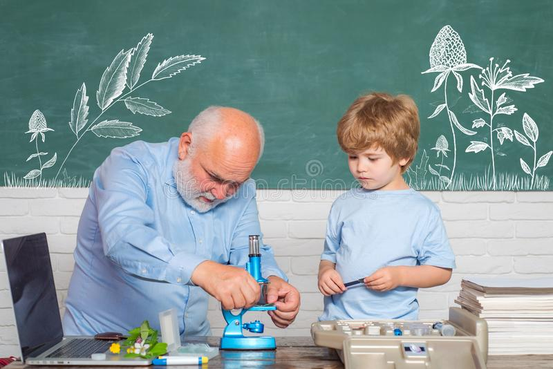 School. Old bearded teacher in the classroom. My Microbiology experiment. Funny teacher in the classroom. Kid from stock image
