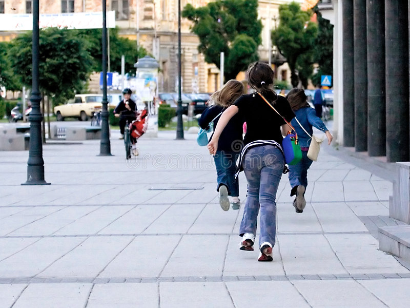 School is over. Girls running from the school stock photo
