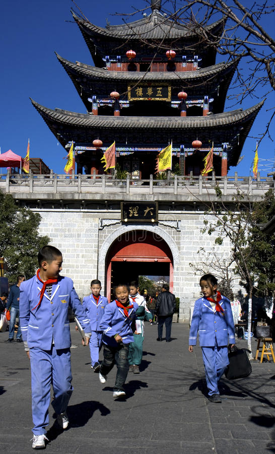 School is over. Schoolchildren in uniform running home on main street of Dali, Yunnan China with city gate in background
