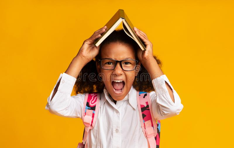 Stressed Schoolgirl Screaming Covering Head With Book Over Yellow Background royalty free stock photos
