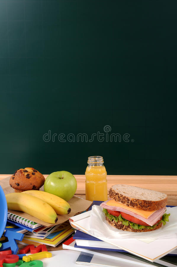 School packed lunch sandwich, apple, drink on classroom desk with blackboard copy space, vertical royalty free stock images
