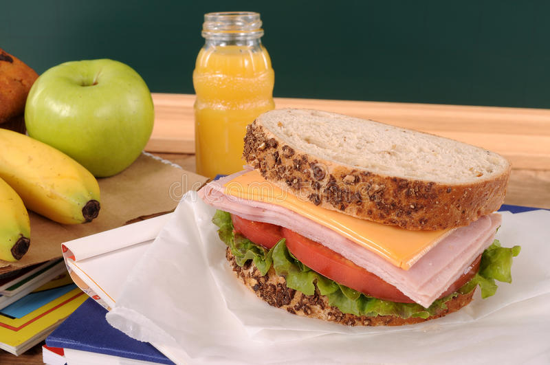School packed lunch, sandwich, apple, drink on classroom desk or table stock images