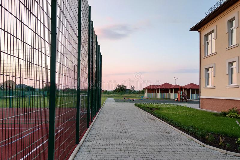 School of preschool building yard with basketball court surrounded with high protective fence royalty free stock images