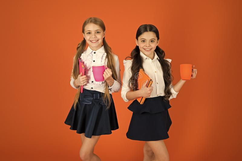 School routine. Having break relax. Drinking tea while break. School mates relaxing with drink. Enjoy being pupil. Girls. Kids school uniform orange background royalty free stock photo