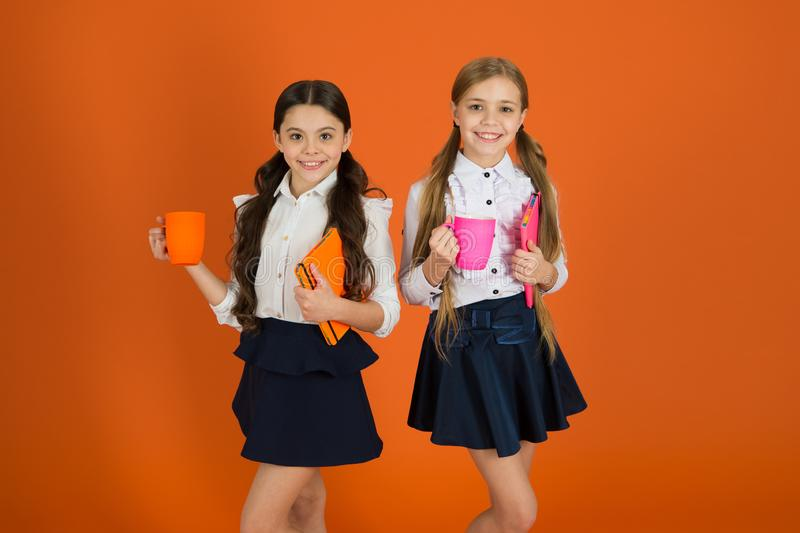 School routine. Having break relax. Drinking tea while break. School mates relaxing with drink. Enjoy being pupil. Girls. Kids school uniform orange background stock image