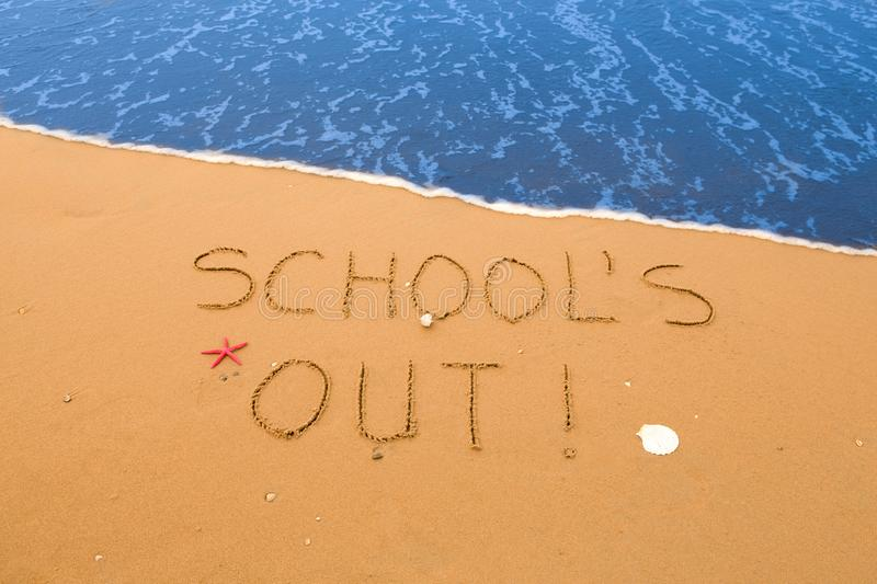 School`s out written in the sand. On the beach near the surf royalty free stock image