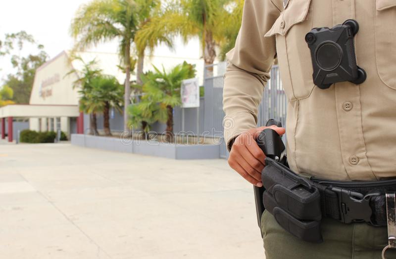 Police officer protecting high school campus. School security concept - armed police officer protecting a high school campus in California royalty free stock images
