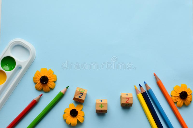 School set- pencils, paints, paper clips, brushes, scissors, autumn flowers on a blue background with space for text. Back to school. office tools. flat lay royalty free stock photos