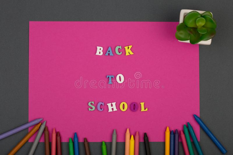 School set with pink paper, text & x22;Back to school& x22; of wooden letters and crayons stock photography