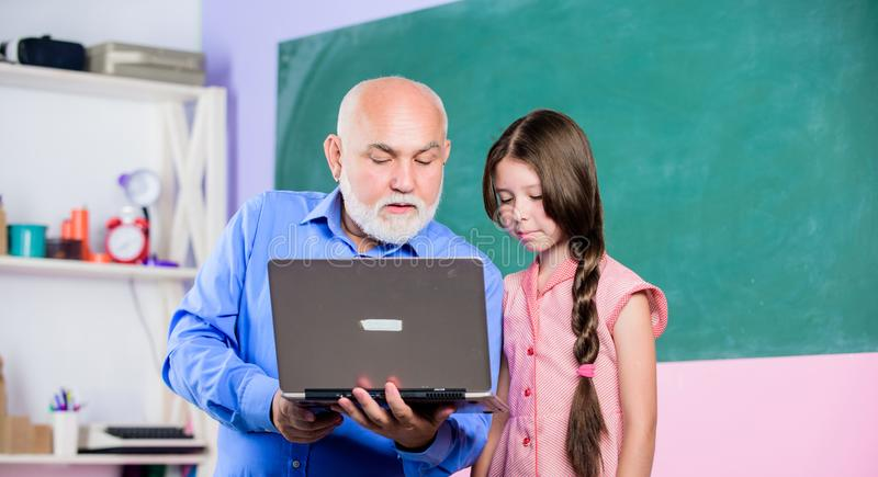School shopping online. cyber monday. online education. Back to school. small girl with man tutor study on laptop. School shopping online. cyber monday. online stock images