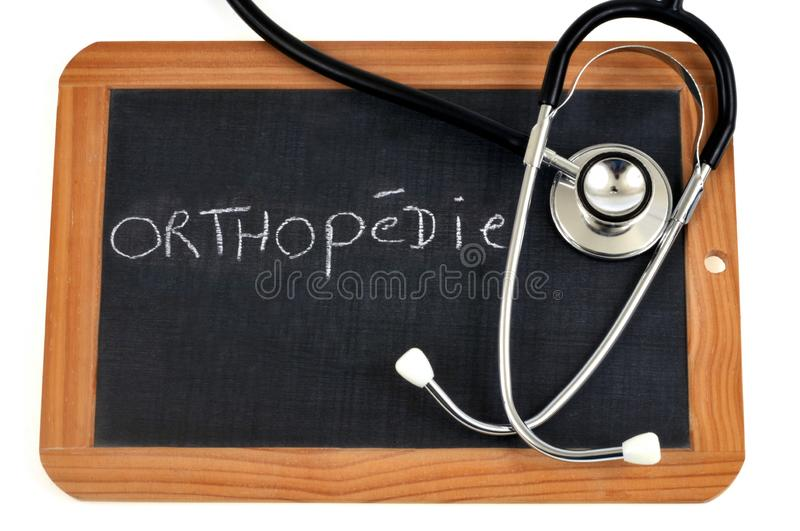 Orthopedic written in French on a school slate. School slate and stethoscope with text written on it stock illustration