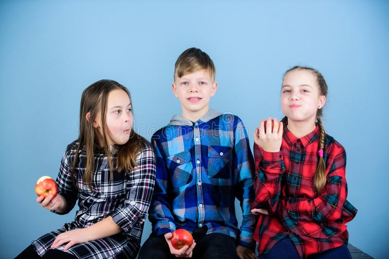 School snack concept. Group cheerful teenagers having fun and eating apples. Teens with healthy snack. Healthy dieting royalty free stock photography