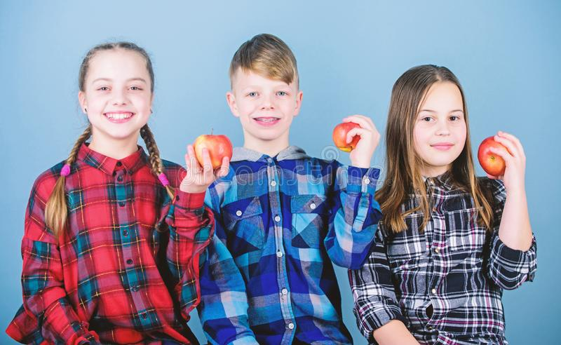 School snack time. Having tasty snack. Boy and girls friends eat apple snack. Teens with healthy snack. Apple fruit has stock photo