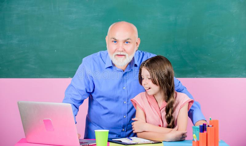 School Spirit. senior teacher help school girl. small girl with man tutor study on laptop. school shopping online. Writing an essay. modern technology in royalty free stock photography