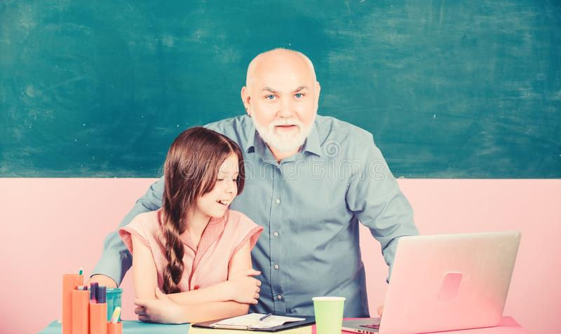 School Spirit. senior teacher help school girl. small girl with man tutor study on laptop. school shopping online royalty free stock images