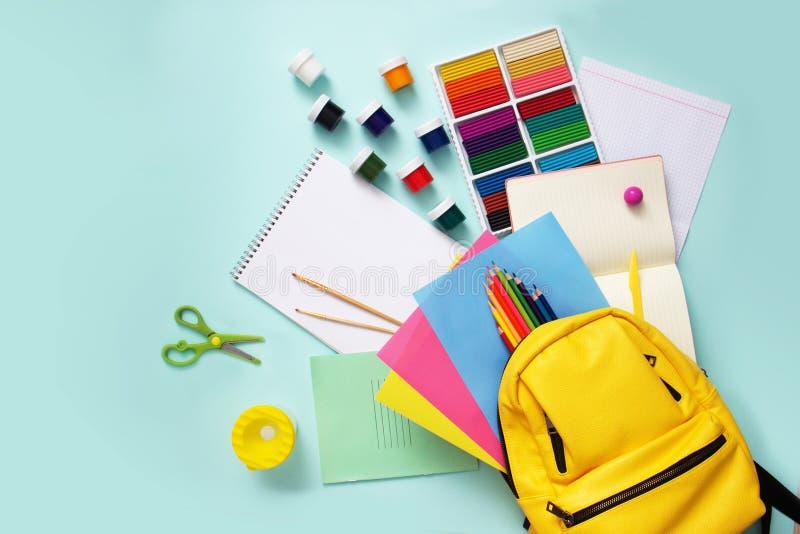 School stationary sets and knapsack on blue background. School stationary sets and knapsack on blue background stock photo