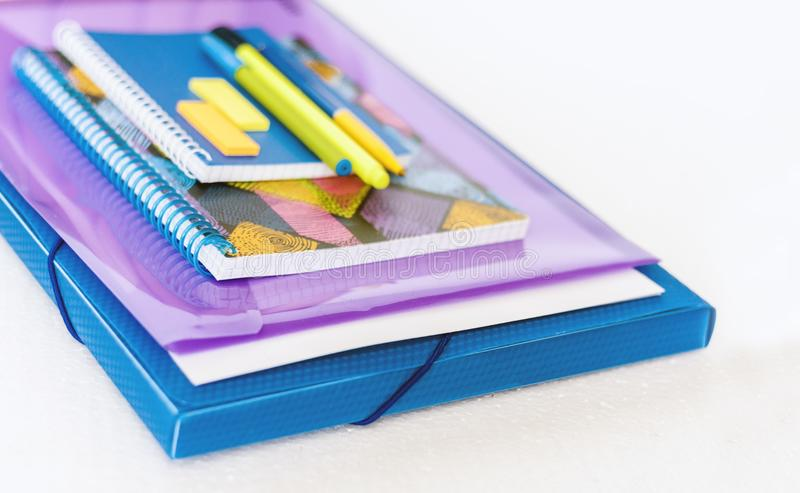 School stationery accessories - notebook, copybook, plastic folder, pens, paper clips, stickers, notepads, education concept royalty free stock photo