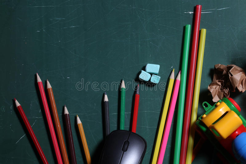 School stationery on desk. Many colorful stationary of pencils for drawing art different colors laying on green school blackboard or desk with computer mouse stock image