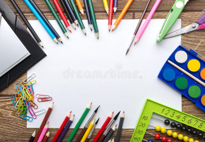 School stationery frame on wooden background: paper, pencil, brush, scissors, folders, abacus, royalty free stock photo