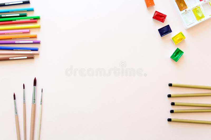 School stationery on pink paper. Colored pencils, pens, pains, paper, brushes for school and student education. Back to school. Copy space. Top view. Flat lay royalty free stock image