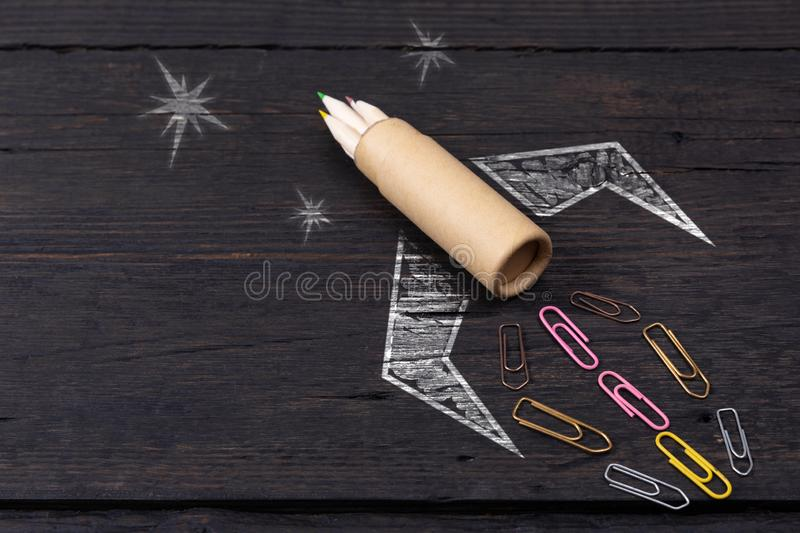 School stationery supplies and hand drawn rocket ship on dark background. Back to school concept. New idea and creativity. Launching  in a natural light stock photos
