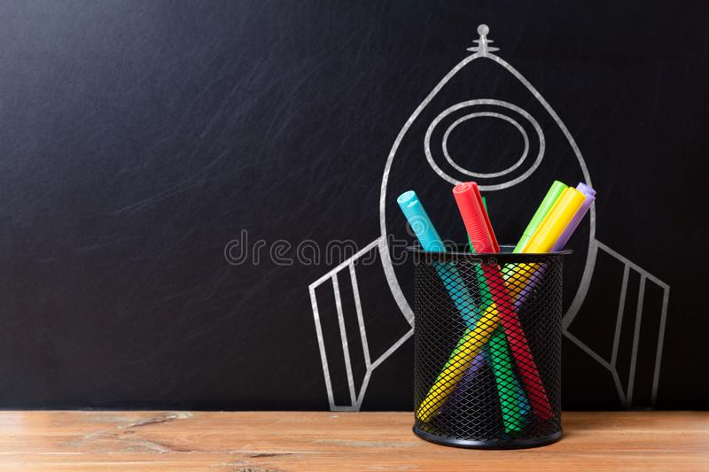 School stationery supplies and hand drawn rocket ship on dark background. Back to school concept. New idea and creativity. Launching  in a natural light royalty free stock photos