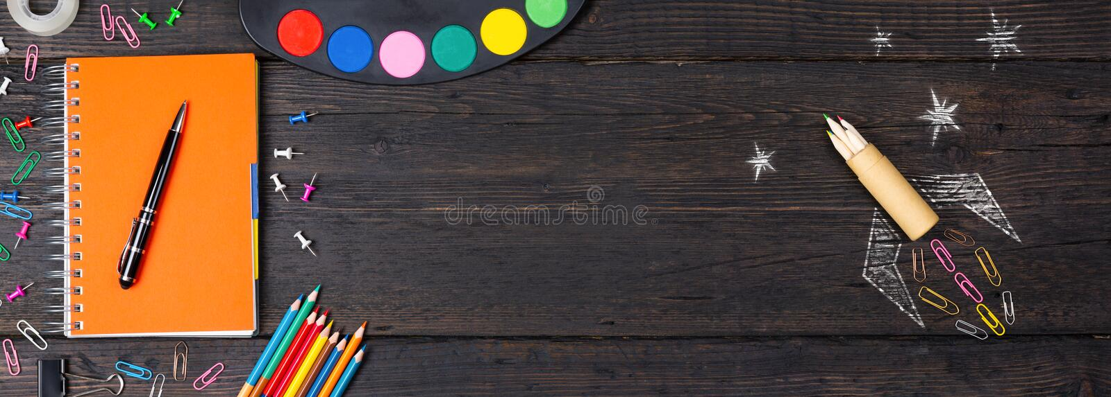 School stationery supplies and hand drawn rocket ship on dark background. Back to school concept. New idea and creativity. Launching  in a natural light stock photography