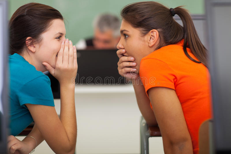 School students gossiping. Cute high school students gossiping in classroom stock photo