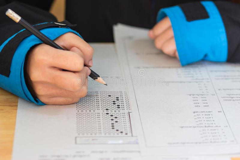 School Students hands taking exams, writing examination room with holding pencil on optical form of standardized test with answers stock photo