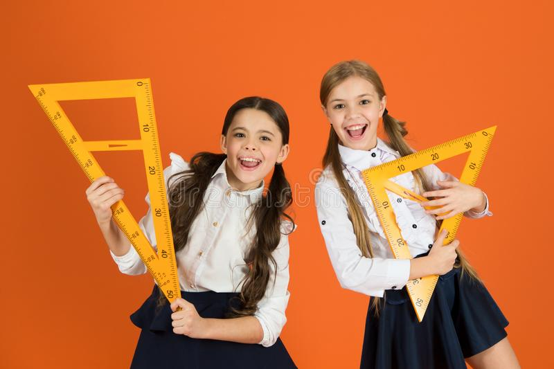 School students learning geometry. Kids school uniform on orange background. Pupil cute girls with big rulers. Geometry royalty free stock image