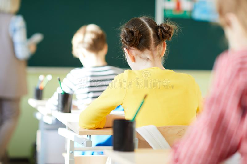 School students writing in workbooks at lesson. Rear view of school students in casual clothing sitting at desks and writing in workbooks while listening to royalty free stock photo