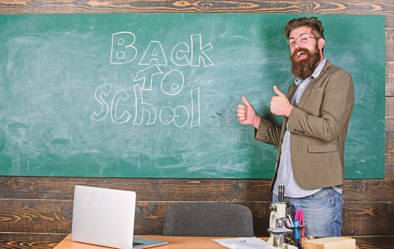 School and studying concept. Teacher or educator welcomes students while stands near chalkboard with inscription back to. School. Ready to teach you. Teacher royalty free stock image